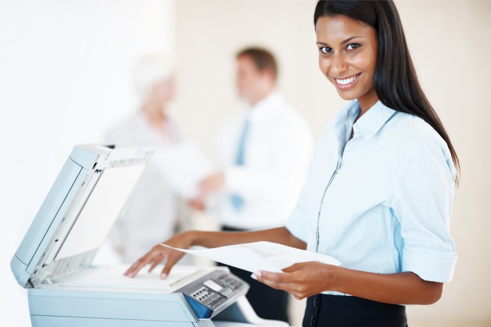 smiling professional at a business printer