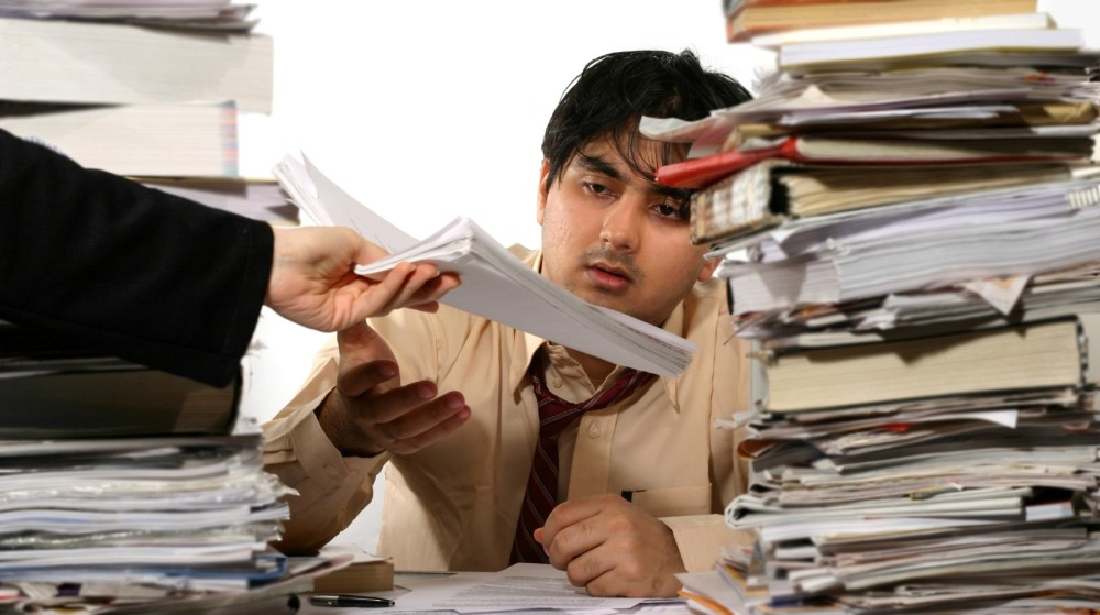 Frustrated office worker starting at piles of unorganized paper documents on a desk