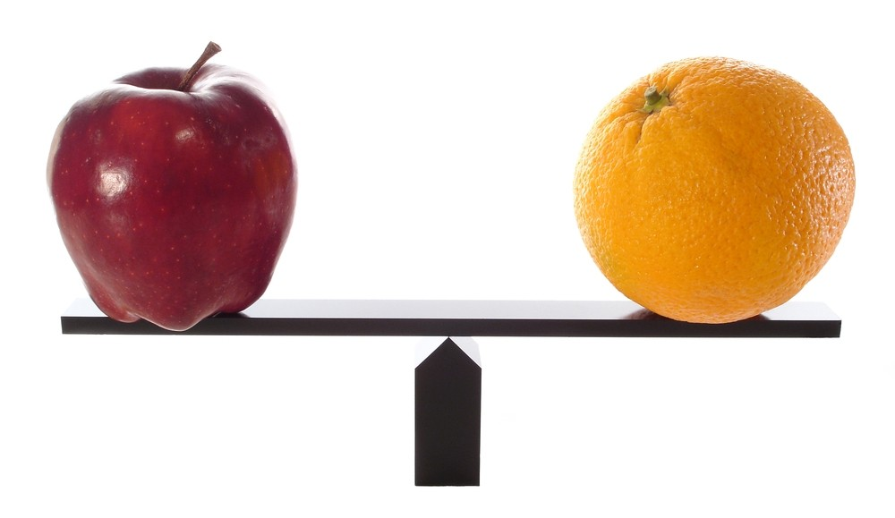An apple on a scale next to an orange