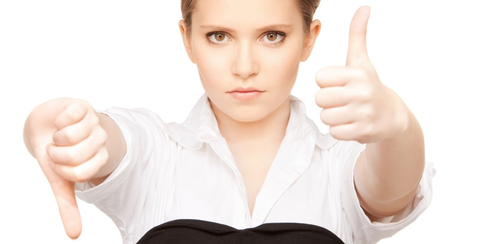 a professional woman holding one thumb up and one thumb down