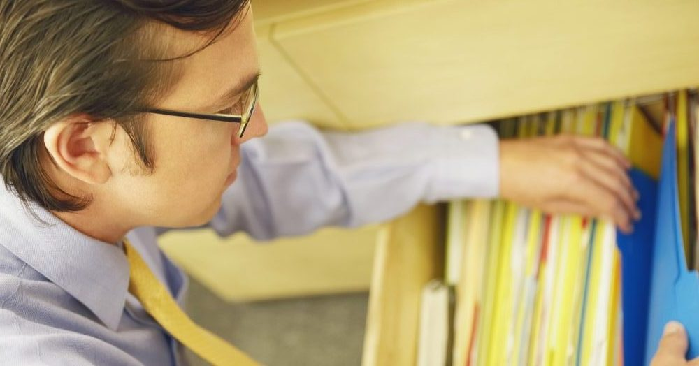 A business man looking through a drawer full of files containing documents