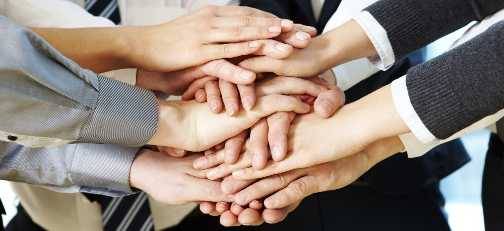 A group of business people coming together to put their hands together in a show of unity