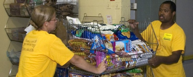 Workers in a food bank pushing a cart full of donated food products