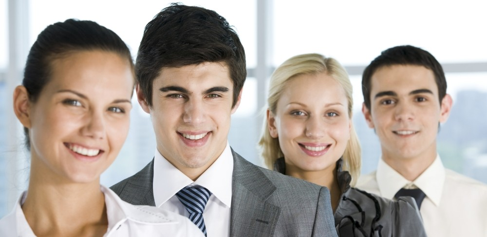 Four smiling business professionals