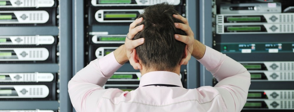 A frustrated IT Professional with his hands on their head looking at network servers