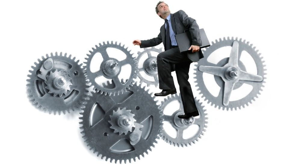 A businessman cycling a gear that is in turn moving other gears