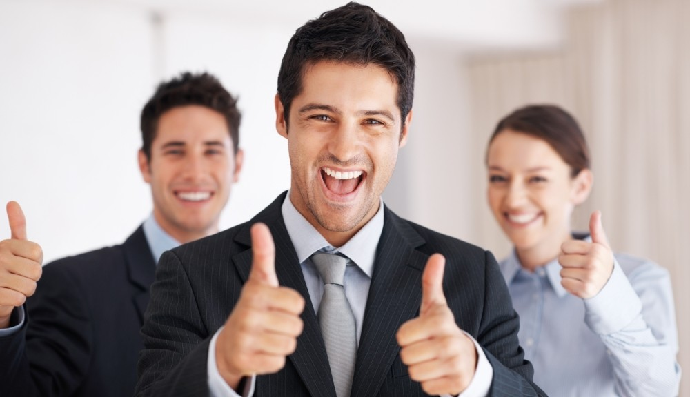 smiling business professionals with their thumbs up showing approval