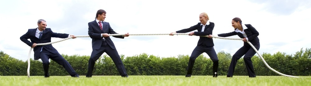 Four business people playing tug of war with a rope