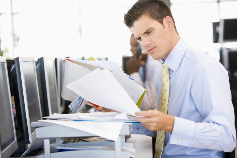 A business professional in an office holding a stack of papers