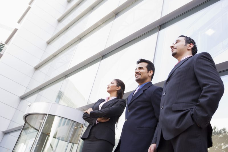 Three business professionals standing outside an office building
