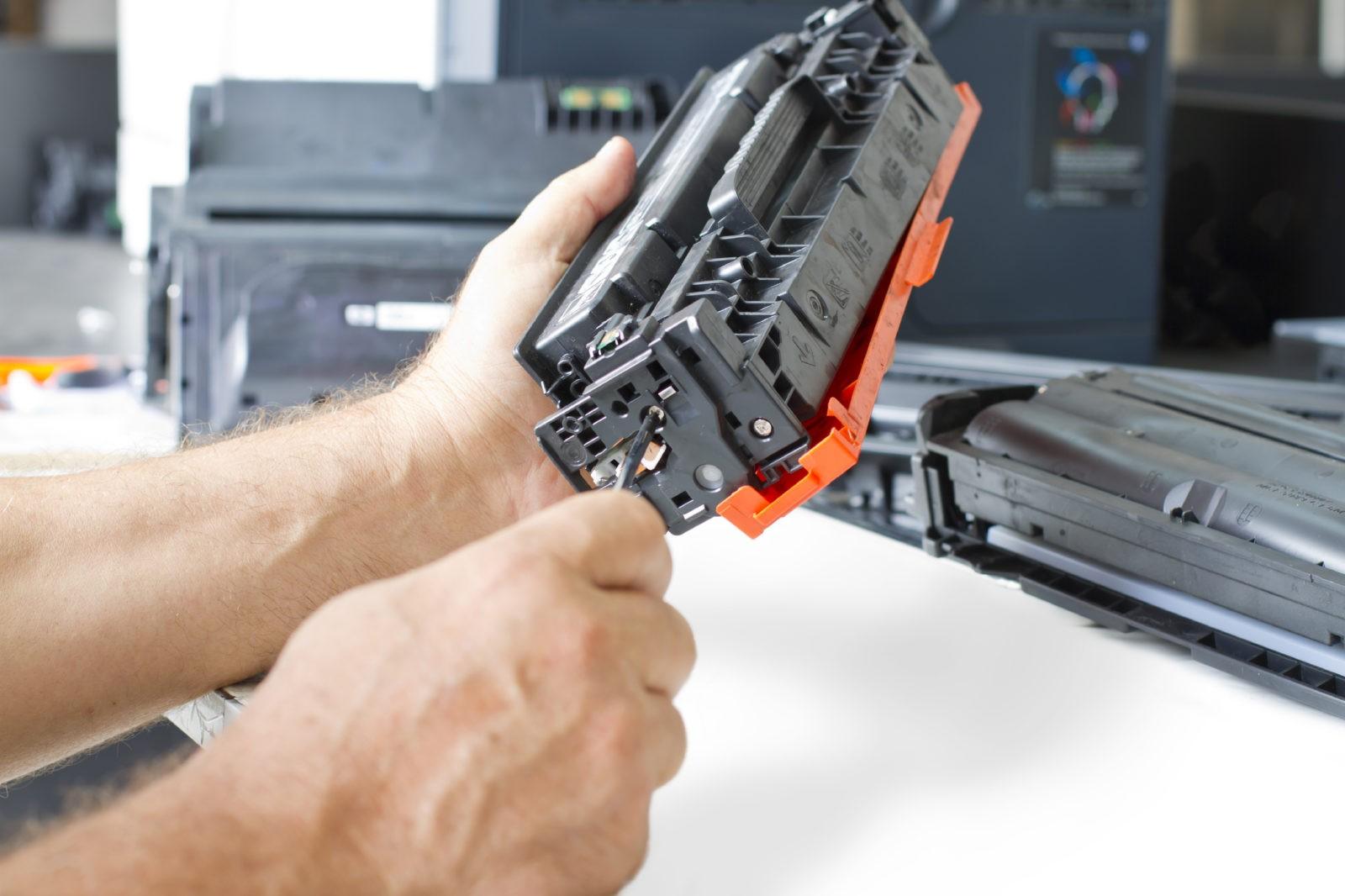 a pair of hands repairing a printer cartridge
