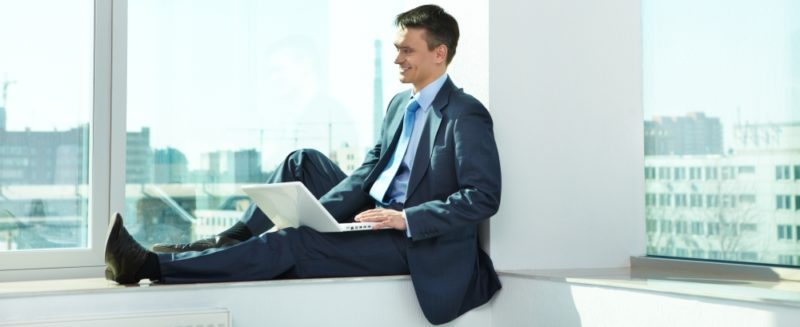 A male business professional sitting in an office with a laptop computer
