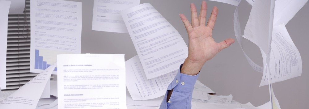 A hand emerging from a massive pile of printed documents