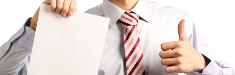 a business professional holding up a piece of paper in one hand giving the thumbs up sign with the other
