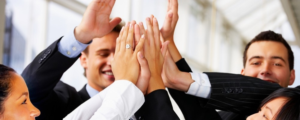 A group of business professionals exchaning a group high-five