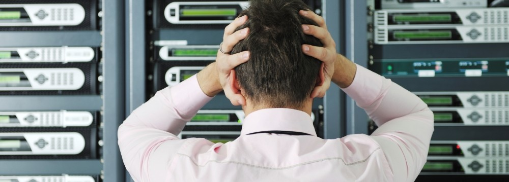 An IT professional staring at a row of network servers with his hands on his head in frustration