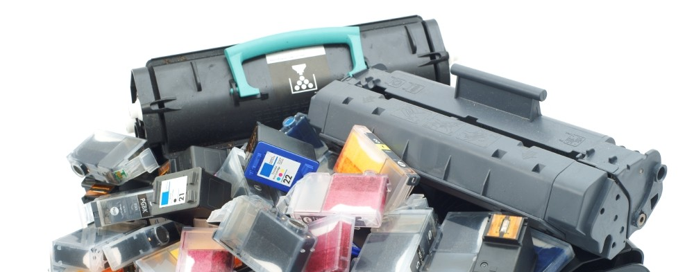 a pile of ink and toner cartridges
