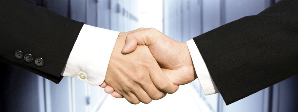 two business professionals shaking hands in a data center