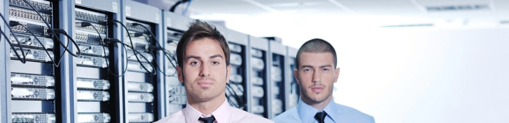 Two IT professionals standing in front of a row of servers