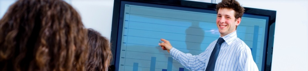 a business professional standing in front of a video touchscreen during a presentation