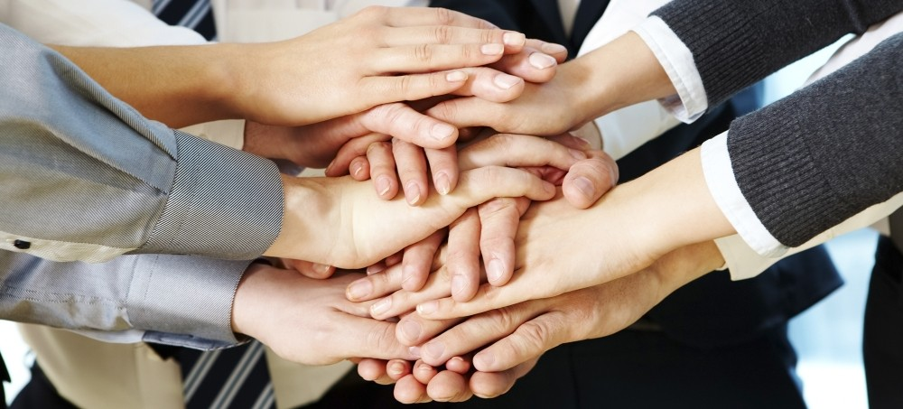 professionals with their hands piled together in a show of unity