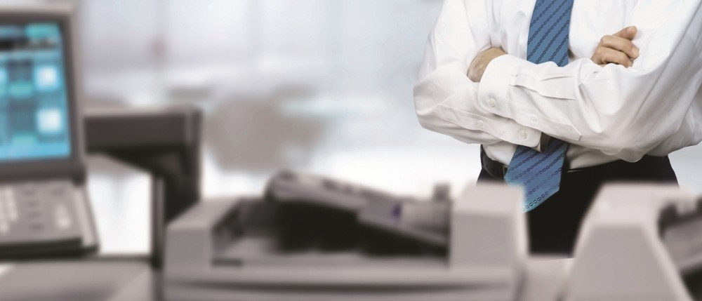 A professional standing over a large multifunction printer in an office