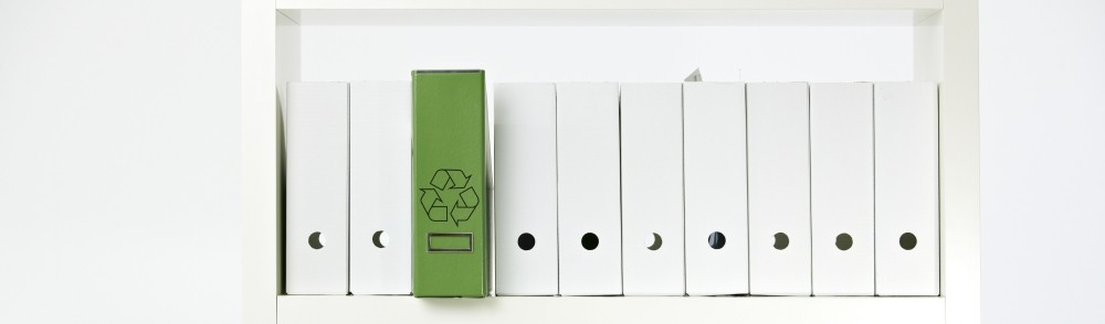a green notebook amongst a row of white notebooks