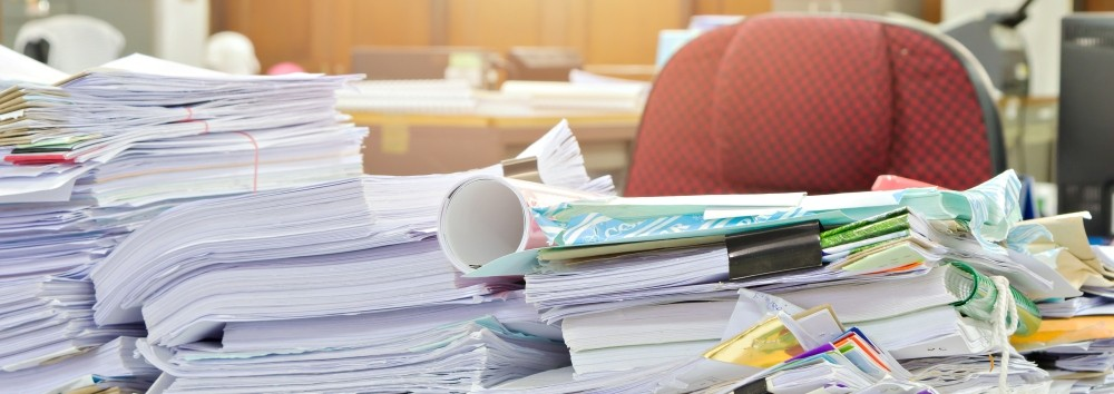 a desk completely covered with piles of paper