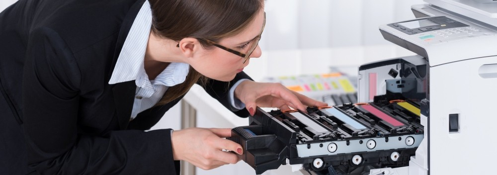 a professional woman looking inside an open office printer