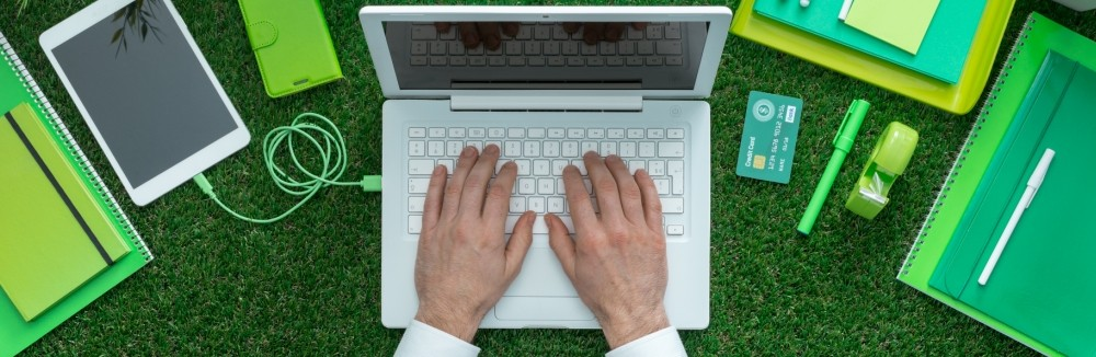 hands at a laptop sitting on top of a bed of grass with green office supplies surrounding it