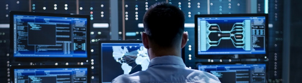 IT professional in front of monitors in a NOC