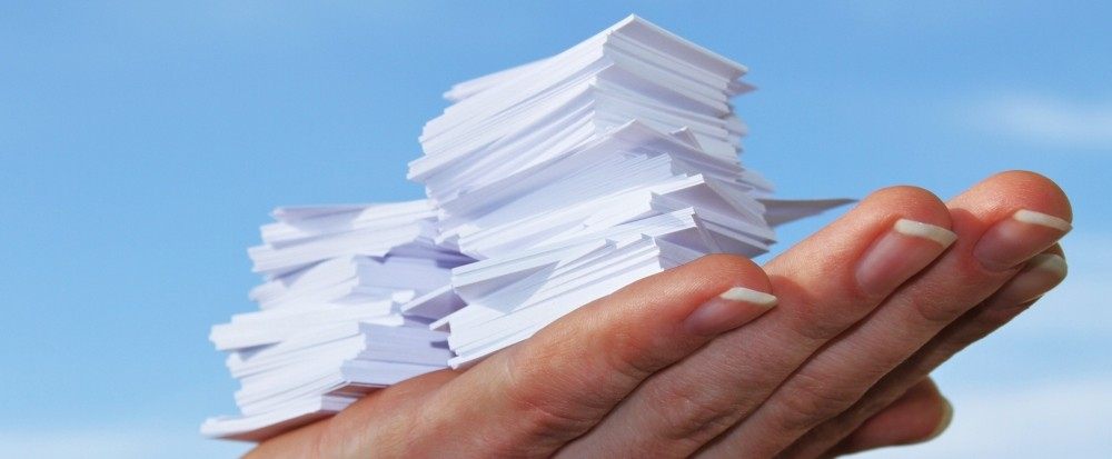 an upturned hand with a stack of papers in the palm