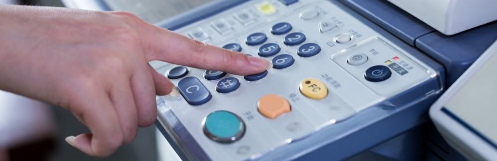 a hand pushing a button on a printer keypad