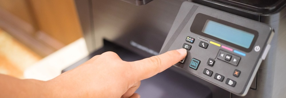 a finger touching an office printer's keypad