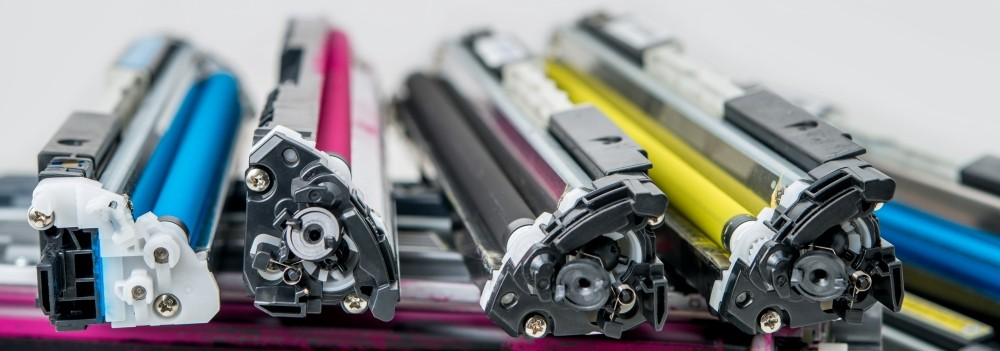 Cyan, magenta, black, and yellow toner cartridges for a printer lying side by side