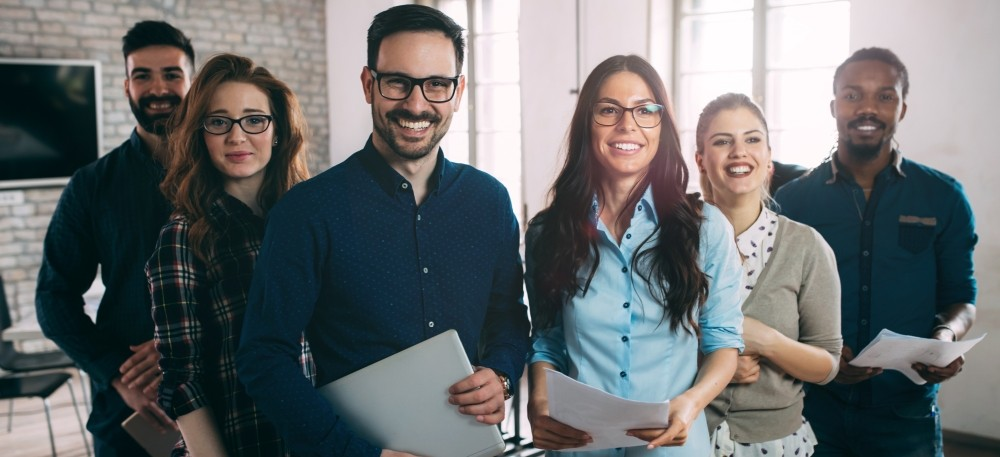 Six smiling professionals in an office holding printed papers