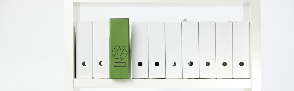 white notebook binders on a shelf with one green notebook binder