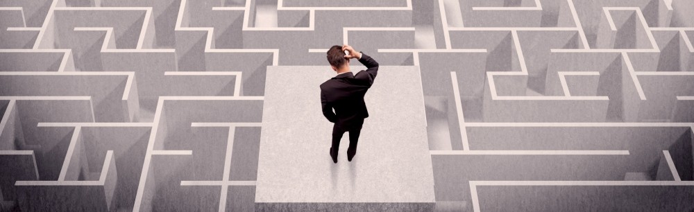 male professional staring at a maze