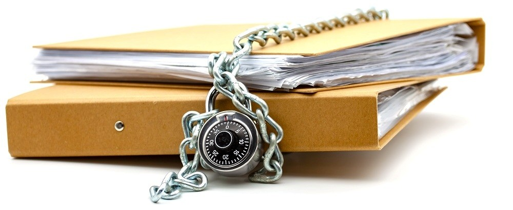 A folder full of paper documents with a chain and padlock around it